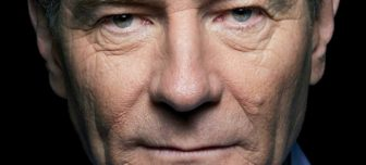 A close up of Brian Cranston. His blue eyes stare intently at the camera. His mouth is a thin line.