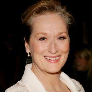 Meryl Streep is smiling at the camera. Her blonde hair is pulled up in a bun. She wears a white jacket with small, dangling pearl earings.