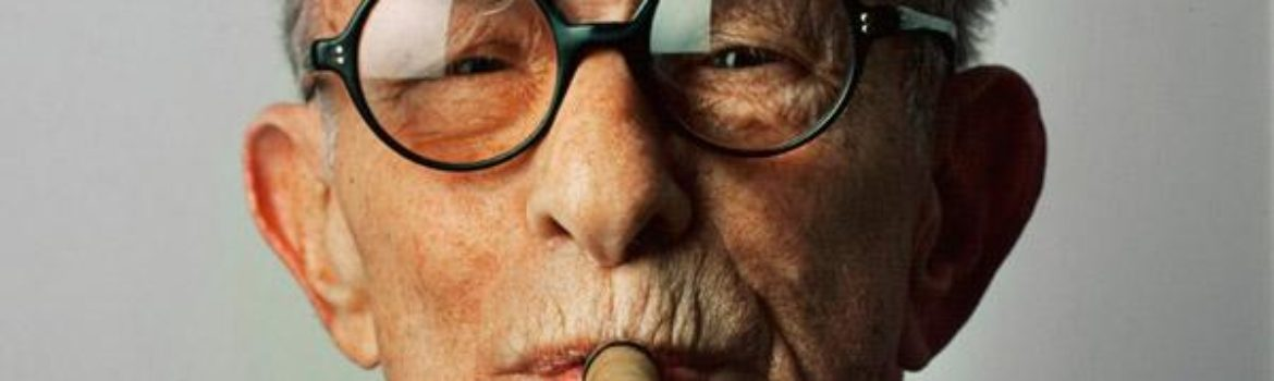George Burns in a close up shot with his black, round glasses on and smoking a cigar.