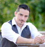 Actor, filmmaker Jason Turner sits in an outside setting with trees in the background. He is wearing a white shirt and grey vest His black hair is combed back and his dark eyes penitrate the camera.