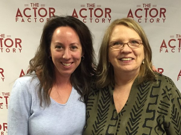 Casting Director Deborah Barylski is standing next to her friend at a film premiere. She is wearing brown framed glasses and a green and black shirt. Behind them is a screen with the words,