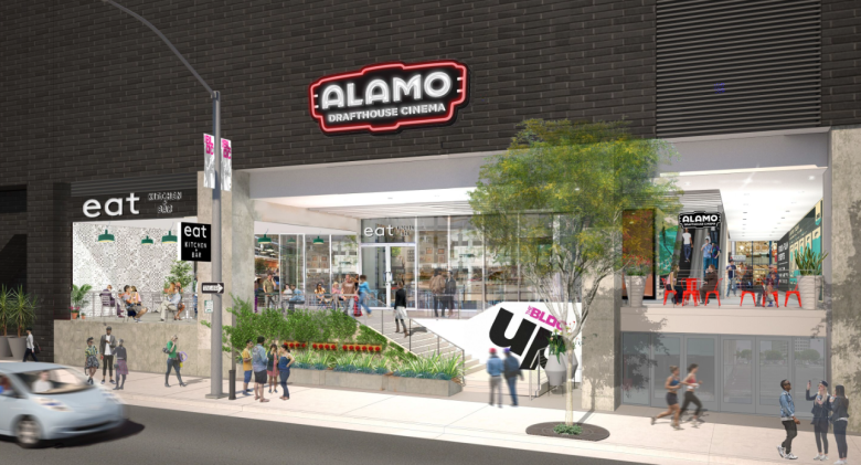A picture of an Alamo Drafthousetheatre with a neon sign of red, black and white featuring the name.