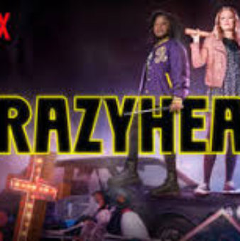 Crazyhead in large, all caps, black and yellow neon letters. Two girls stand side by side each holding a shovel and a stake, standing on top of a junky car with piles of junk and a neon cross leaning against the car.