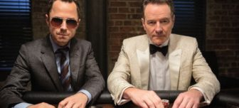 Actors Giovanni Ribisi and Brian Cranston are sitting at a poker table holding cards and staring at the camera. Giovanni is wearing a dark gray suit and stipped tie and sunglasses. Cranston is wearing a white tux with black bow tie.