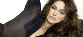 Actress Keira Knightly is shown lounging, relaxed with her arm above her head. She is wearing a black zip up top that blends well with her dark hair.