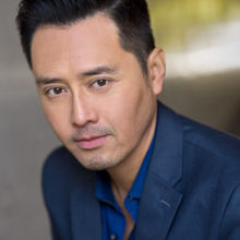 An Asian man looks at the camera intently. He's wearing a dark blue collared, button down shirt.