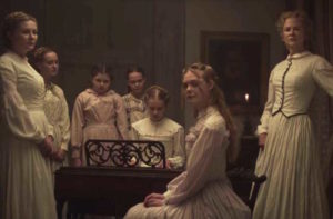 The women of The Beguiled gather around the piano in anticipation of a small concert for the corporal. They are in Civil War period clothing, mostly whites and pale pinks in a darkened, cepia toned room.