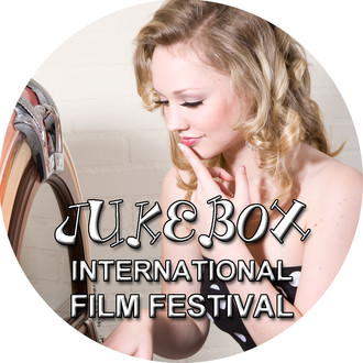 A beautiful blonde woman stares at a jukebox with her finger on her lips as she tries to choose a song. The logo of Jukebox International Film Festival appears overlayed on the picture.