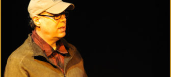 Larry Moss appears in a black background wearing a light brown jacket, beige baseball cap and black glasses. He appears to be looking at someone off camera.