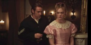 The injured soldier, Colin Farrell leans in to a young lady played by Elle Fanning, in a sujestive manner. He is dressed in his Union uniform and she in a pale pink dress with lace around the neck. She casts a glance back, aware of his not so subtle pressence.