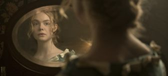 Elle Fanning, a young and beautiful girl stares at her reflection in an oval mirror on her dressing table. She is dressed in a late 19th century pale blue dress with her hair upswept, tendrils hanging down.