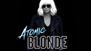 Actress Charlize Theron stands in a black and white picture wearing a black trench coat and dark sunglasses. The word atomic is in icy blue and blonde in white neon.