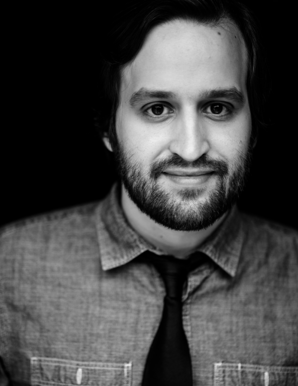Actor Ben Auxier poses for his black and white headshot photo. He's wearing a button down jean shirt with a black tie. His deep brown eyes and easy smile are accentuated by a black background.