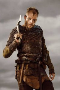 Floki stands before us in his brown armor wielding an ax. His hair is short and he wears a goatee. He puts black charcoal in lines around his eyes and down his face.