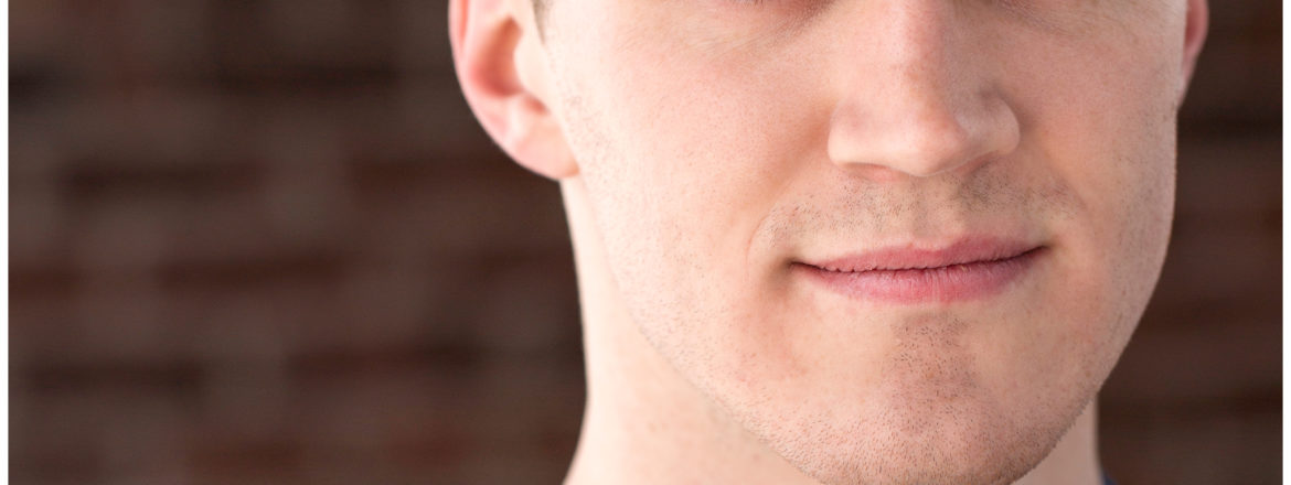 A close up picture of actor Seth Macchi. He's wearing a navy blue tee-shirt. His bright blue eyes reflect the color of his shirt and he smiles effortlessly at the camera.