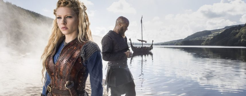 Sheild Maiden Lagertha and King Ragnar stand on the edge of the sea with their Viking ship in the background.