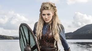 Lagertha stands before us is a brown leather warriors garb weilding a Viking wooden shield and looking fiercly into the camera. He long blonde hair is kept long except for the front which is intricately braided.
