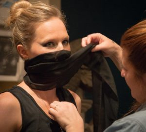 A young blonde girl is having a mask put on her by a make up artist on set.