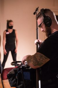 A picture of the cinematographer, Nicholaus James on set wearing headphones. There is a girl in the background dressed in black, and wearing a mask.