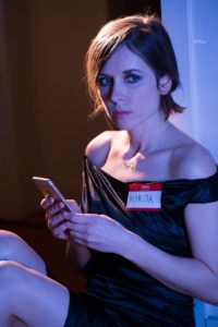 "A pretty woman with dark brown hair and dark eyes looks furtively to the side while holding her phone. She's wearing a short black dress, ""La Femme Nikita"" style."