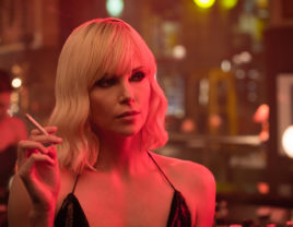 Actress Charlize Theron stands in a bar wearing a strapy little black number and smoking a cigarrette.