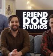 The three guys from Friend Dog Studios sitting on a couch with a tv screen behind them reading,