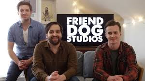 """The three guys from Friend Dog Studios sitting on a couch with a tv screen behind them reading, """"Friend Dog Studios""""."""
