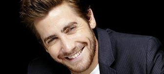 A close up picture of actor Jake Gyllenhaal smiling sheepishly at the camera.