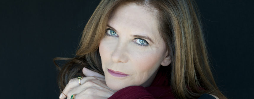 A close up of Ivana Chubbuck. Her brown hair falls about her shoulders. Her bright blue eyes penetrate the camera.