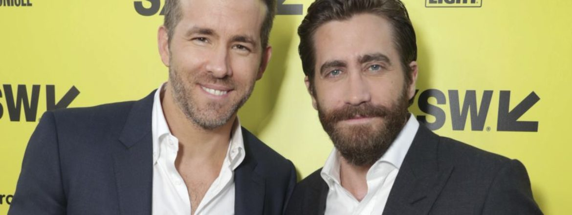 Actors Ryan Reynolds and Jake Gyllenhaal attending a film premiere, both wearing white shirts and black suit jackets.