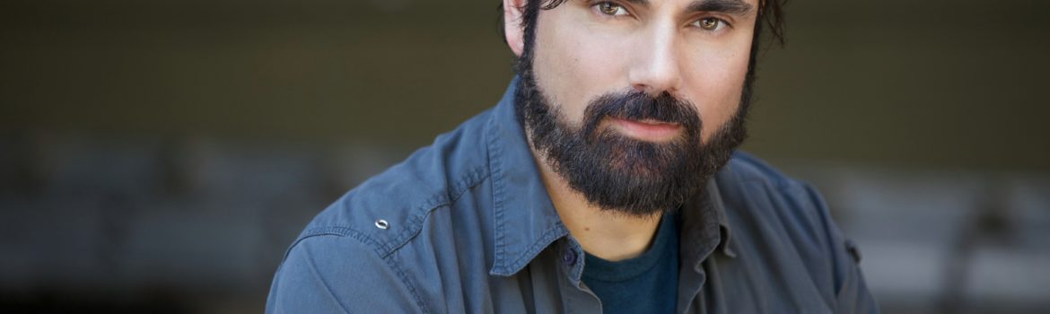 A picture of Actor Scott Vinci wearing a blue tee-shirt and blue overshirt. He has black hair, cut short and hazel eyes. He's sporting a cool black beard.