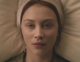 A picture of the main character of Alias Grace with her head on a pillow, bonnet on, staring straight up at the camera.