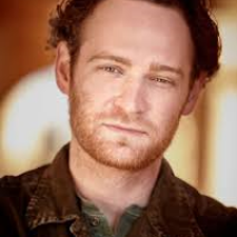 A headshot of actor Chris Bylsma in cepea tones, wearing a brown colared shirt.