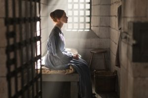 A pictures of the beautiful, young Grace Marks sitting in her prison cell illuminated by a stream of light from the barred window. She is dressed in 1840's period clothing.