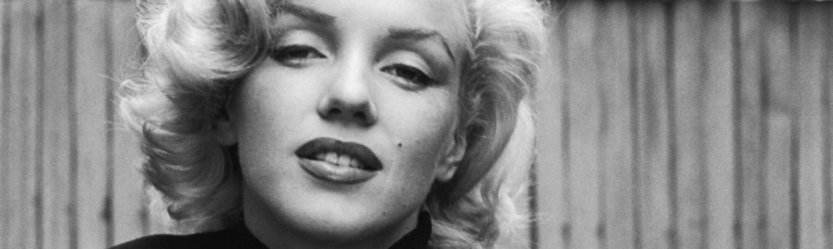 A black and white picture of Marilyn Monroe in a black turtle neck.