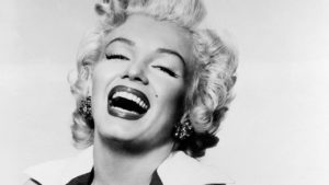A black and white picture of Marilyn Monroe laughing.