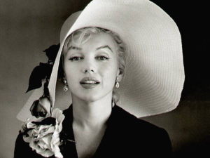 A black and white picture of Marilyn Monroe with a huge white hat on.
