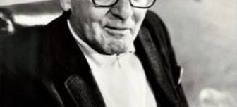 A black and white picture of acting teacher Sanford Meisner, sitting smoking a cigarrette.