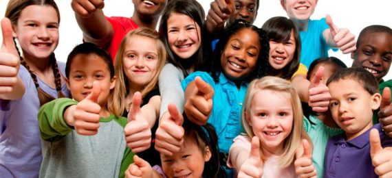 A picture of a group of kids, huddled together, smiling and giving the thumbs up.