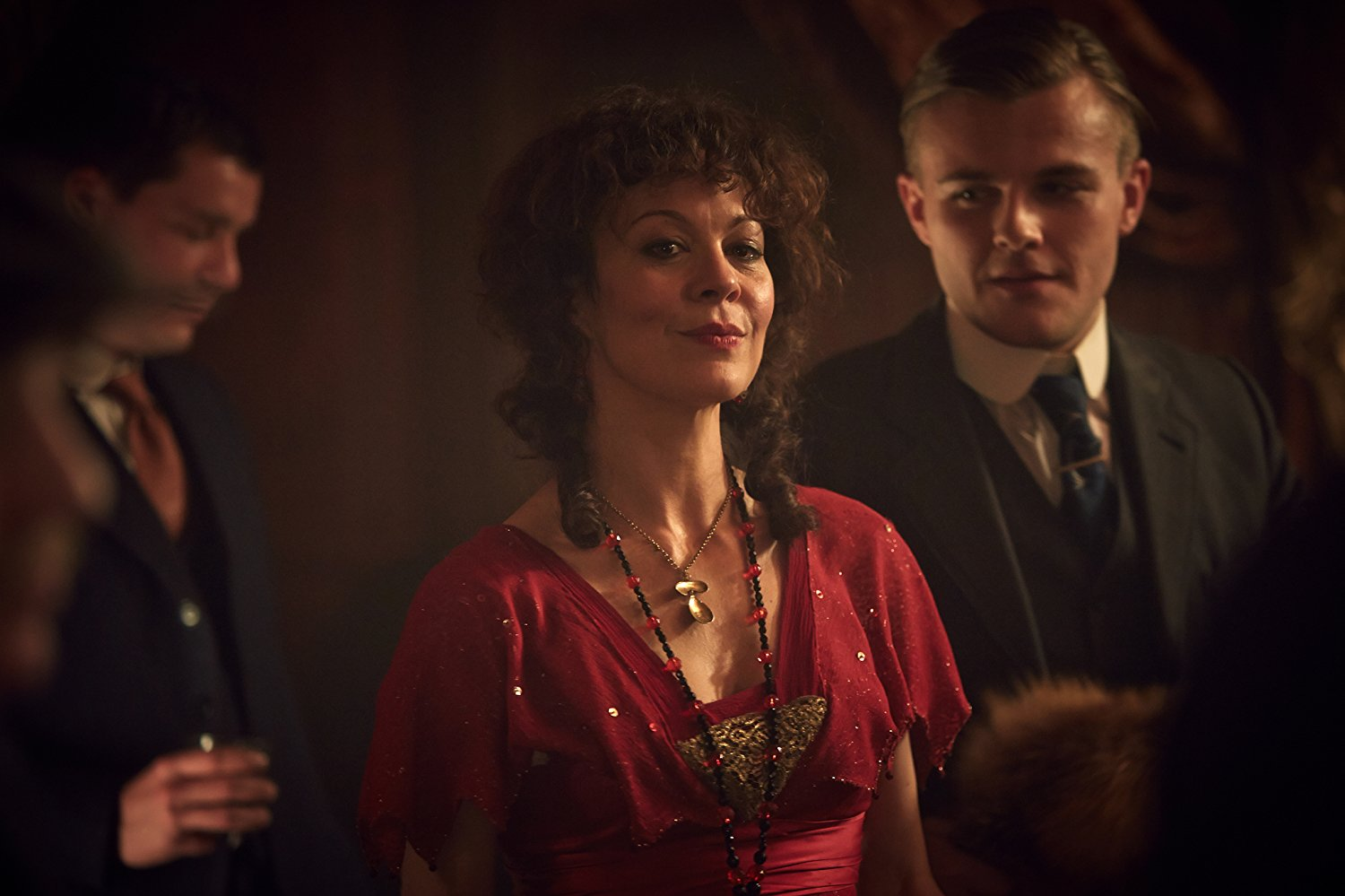 A picture of Helen McCrory as Aunt Polly in the Peaky Blinders. She is dressed in a red Gypsy dress and her dark hair durls around her face.