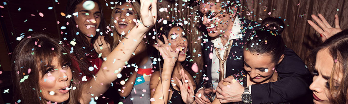 A picture of young men and women dancing at a New Year's Eve party with confetty raining down on them.