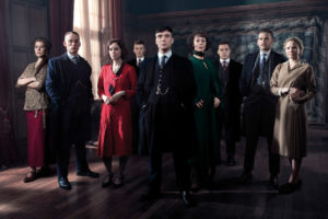 A picture of the cast of Peaky Blinders dressed in 1920's period clothing and standing in a darkened room looking at the camera.