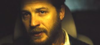 A close up picture of actor Tom Hardy sitting in a darkened car, tearing up.