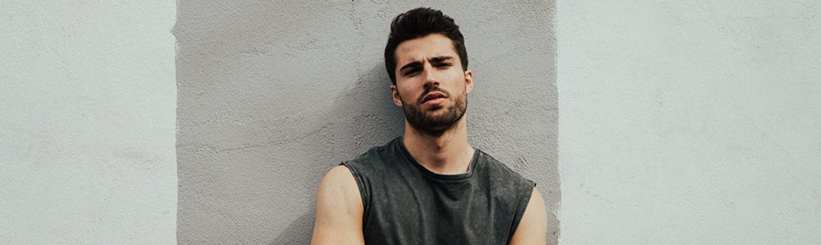 A picture of actor Aslessandro Marino standing against a wall. He's wearing a dark grey tee-shirt with the sleeves cut off showing his muscular arms crossed at his chest.