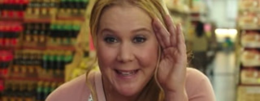 An image of Amy Schumer smiling and looking cute with her blond hair tied back, hiding her face from someone.