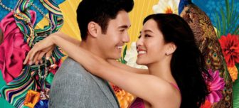 A picture of actors Henry Golding and Constance Wu with their arms around each other, smiling at each other. Colorful Chinese pictures are in the background.