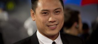 A picture of director Jon M. Chu in a black suit and tie, smiling at the camera.