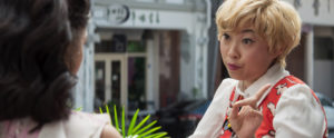 A blonde Awkwafina gives advice to her best friend, Rachel (Constance Wu) while lunching outside in Singapore.