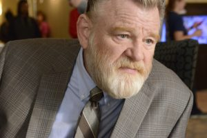 A picture of Brendan Gleeson as Detective Bill Hodges. He has greying hair and a white beard, blue eyes and a furrowed brow.