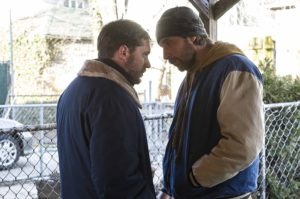 A picture of Tom Hardy and Matthias Schoenaerts standing on a front porch in winter, confrontational stances.